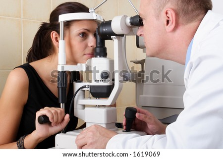 Eye doctor performing an eye examination - stock photo