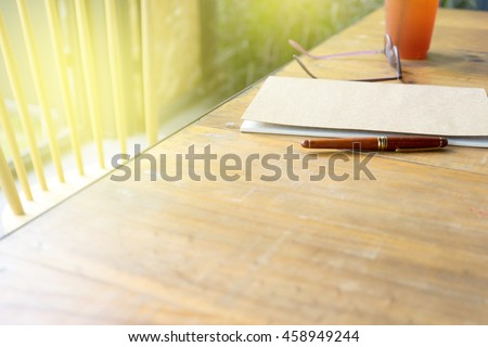 eye glasses and pen on paper note book on wood table with copy space.