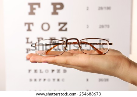 Eye glasses in female hand on eyesight test chart background
