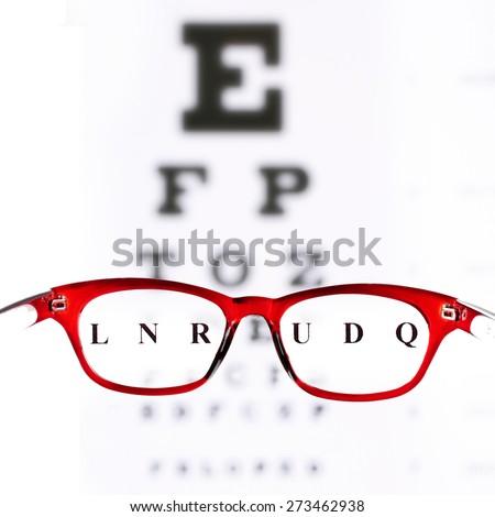 Eye glasses on eyesight test chart background - stock photo