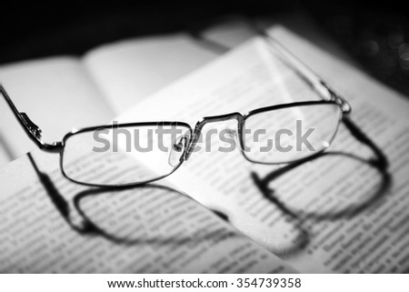 Eye glasses on open book, close up