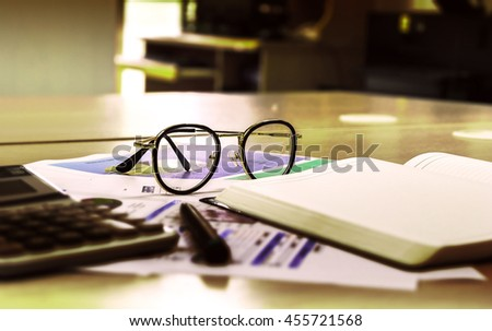 eye glasses on wooden office desk with open diary book and data chart,business concept,vintage style