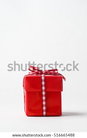Eye level shot of a square Christmas gift box with lid, wrapped in red paper and tied to top with gingham ribbon bow.  Copy space above.