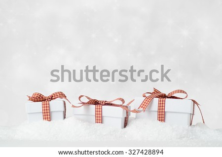 Eye level shot of three white Christmas gift boxes with lids, in a row and bow tied with gingham checked ribbons, nestling in artificial snow with sparkly star bokeh background. - stock photo