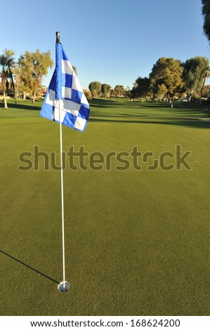 Eye level view of a golf green with a checkered flag - stock photo
