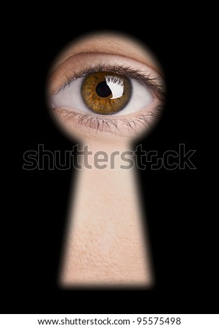 Eye looking through a blured black keyhole - stock photo