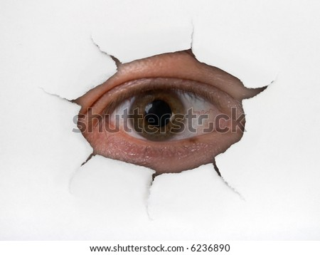 Eye looking through hole on paper surface - stock photo