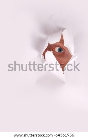 eye looking through paper hole. - stock photo