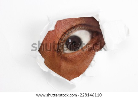 Eye looking through torn white paper - stock photo