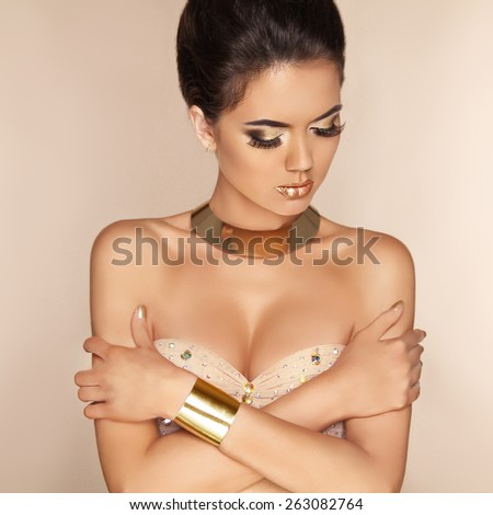Eye Makeup. Beautiful Glamour fashion model girl in luxurious golden jewelry. Attractive brunette young woman in dress posing over beige background. - stock photo