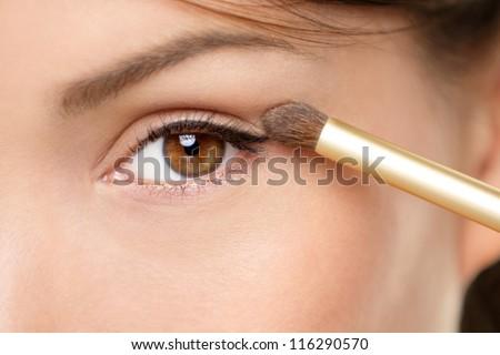 Eye makeup woman applying eyeshadow powder. Woman putting shadow powder on eyes with makeup brush. Closeup of eyelid and eyebrow. - stock photo