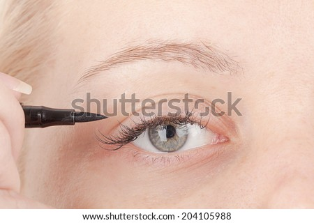Eye makeup woman applying pen - stock photo