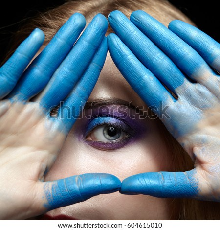 Eye of Providence eye pyramid Illuminati and mason symbol made of hands and female face with blue paint on fingers