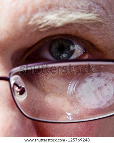 Eye of the businessman, natural reflexion in eyes and glasses - stock photo