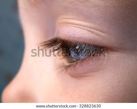 Eye of the child close-up, with a spout - stock photo