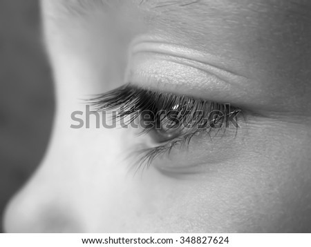 Eye of the child close-up, with a spout, photo is in black and white. - stock photo