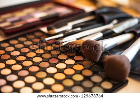 Eye shadow palette in natural colours and make up brushes - stock photo