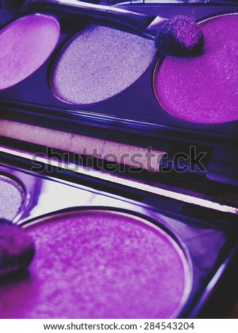 Eye shadow palette with reflection in the mirror close up and selective focus.