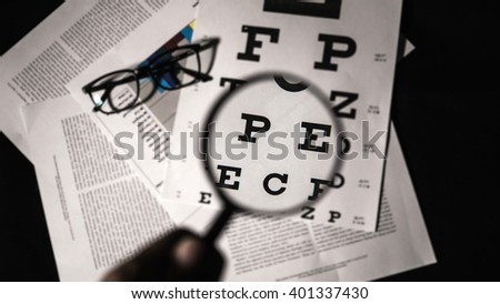 Eye test examination with a magnifier. - stock photo