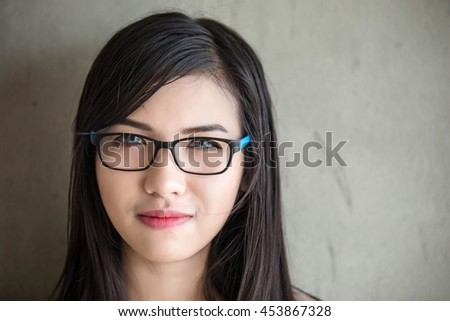 Eye wear glasses woman closeup portrait.Asian woman wearing glasses, standing in the dark. - stock photo