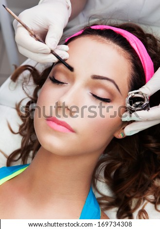 Eyebrows tinting treatment with natural henna dye - stock photo