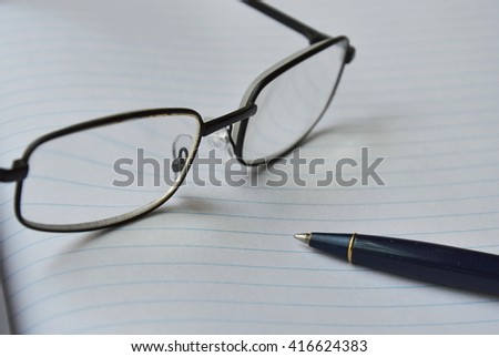 eyeglass and pen on the book