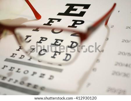 eyeglasses and eye chart close-up on a light background - stock photo