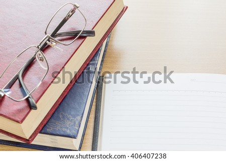 Eyeglasses and Notebook open blank page on wood table - stock photo