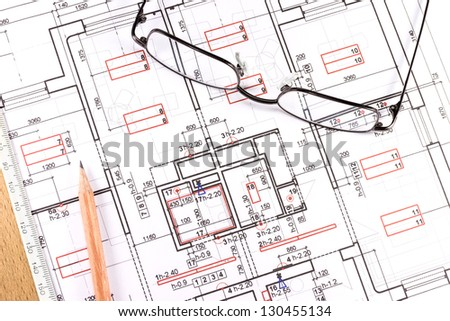 Eyeglasses and pencil on construction blueprint