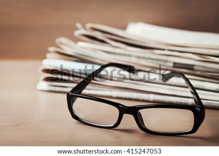 Eyeglasses and stack of newspapers on wooden desk for themes of ophthalmology, poor vision and reading