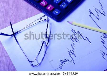 eyeglasses, calculator, pencil and diagram on a table