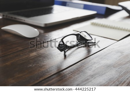 eyeglasses, laptop computer and notepad on wooden office desk