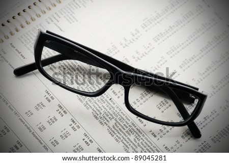 Eyeglasses laying down on a business document, business still-life with vignette. - stock photo
