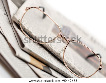 Eyeglasses lie on a pile of newspapers. A photo close up. Selective focus - stock photo