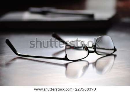 eyeglasses on a desk - stock photo