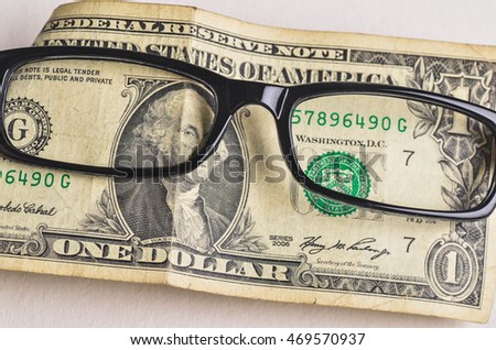 eyeglasses on a one dollar banknote as a sign of focus on business philosophy