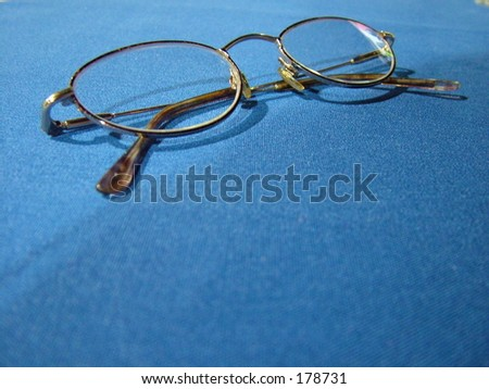 Eyeglasses on blue tablecloth - stock photo