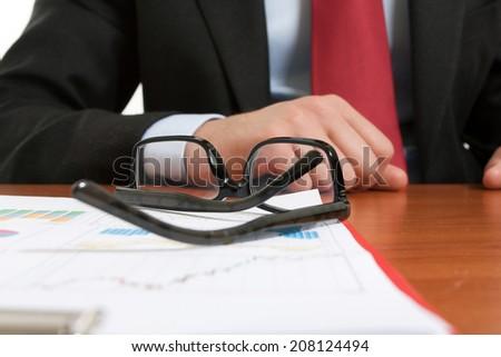 Eyeglasses on business documents - stock photo