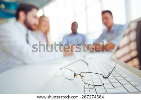 Eyeglasses on laptop keypad with group of partners on background - stock photo