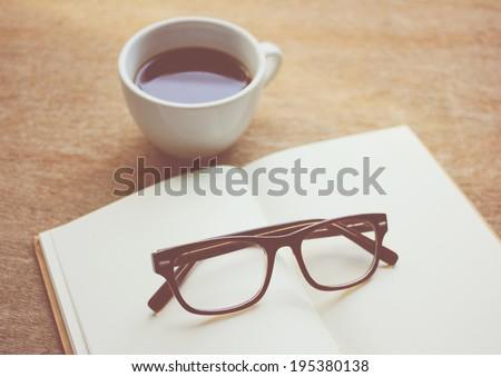 Eyeglasses on notebook and black coffee, nostalgic still life, retro instagram filter effect - stock photo