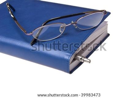 eyeglasses on organizer with pen isolated on white background - stock photo