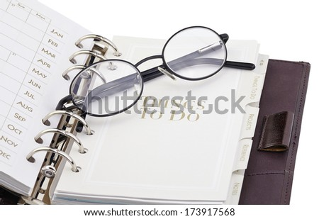 """Eyeglasses on the page """"what to do"""" of the personal organizer - stock photo"""