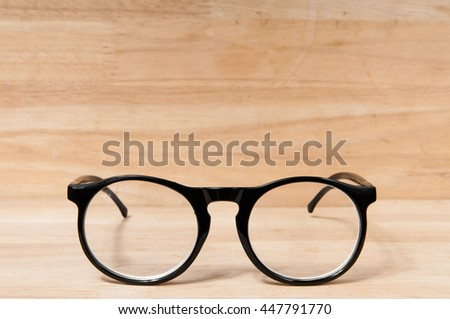 Eyeglasses on wooden table.