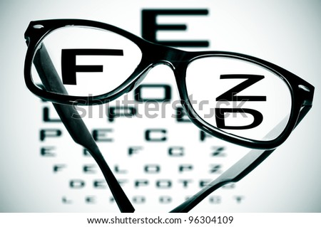 eyeglasses over a blurry eye chart