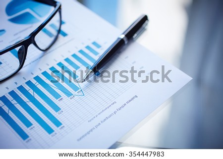 Eyeglasses, pen and financial document on workplace