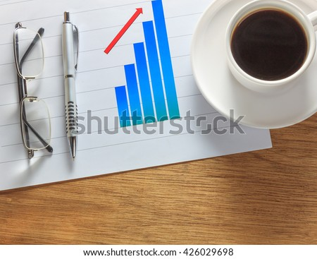 eyeglasses,pen,cup of coffee on chart.Chart on wood table background. - stock photo