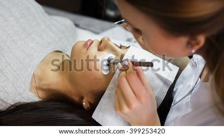 eyelash extension procedure - master and a client in a beauty salon