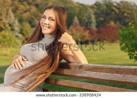 Eyes full of happiness. Beautiful happy pregnant woman smiling to the camera sitting outdoors on a warm day - stock photo
