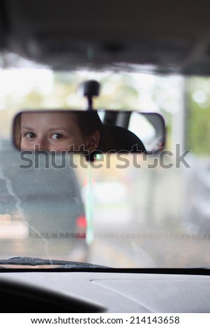 Eyes of a young driver in rear-view mirror  - stock photo