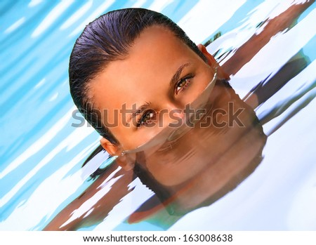Eyes of beautiful women swimming in the pool - stock photo